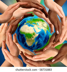 Beautiful conceptual symbol of the Earth globe with multiracial human hands around it. Unity and world peace concept.