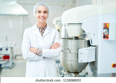 Beautiful confectionery factory worker standing in white coat with arms crossed smiling and looking at camera.