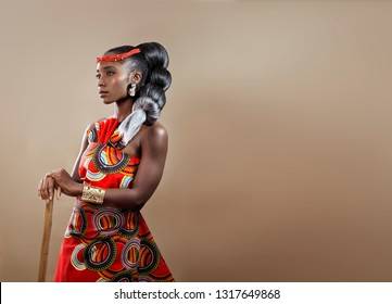 Beautiful confident African woman with intricate hair wearing an African print dress holding a wooden stick confidently