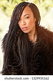 Beautiful confident African woman with intricate long braided hair wearing a faux fur coat outside