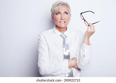 Beautiful confident blonde businesswoman holding eyeglasses, posing in studio.