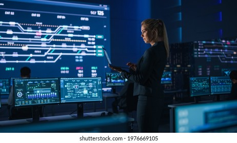 Beautiful Confident Female Project Manager works on a Laptop Standing in Telecommunications System Control Room. In Background Screen Showing Infographics of Infrastructure, Charts, System Analysis
