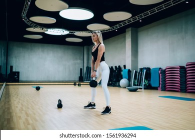 Beautiful confident focused athletic female in sportswear squatting with kettlebell standing in gym with sport equipment in front of mirror