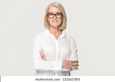 Beautiful confident mature middle aged businesswoman in glasses looking at camera posing isolated on white grey studio background, smiling older senior female professional lawyer business portrait