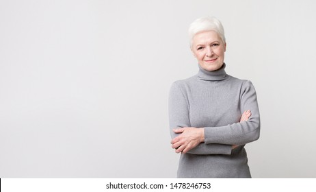 Beautiful confident senior woman with crossed hands smiling at camera, light studio background, panorama with copy space
