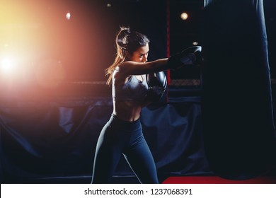 Beautiful, confident woman boxer athletic wearing gloves strikes punching bag during training preparation for battle. Bright flash of light in background