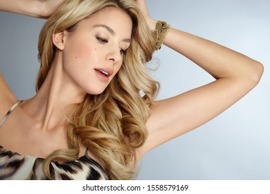 Beautiful confident woman with long blond hair wearing animal print dress over gray studio background.