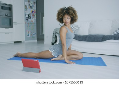 Beautiful confident woman in shorts stretching body on mat while watching tutorial video with yoga practice using tablet.