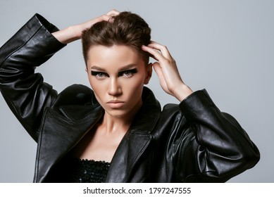 Beautiful confident woman with strong face, short hair, bold eyeliner makeup, wearing black trendy leather jacket, posing on grey background. Close up studio fashion, beauty portrait