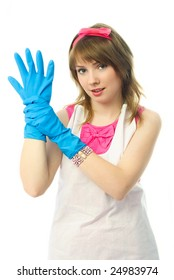 beautiful confident young housewife putting on blue rubber gloves