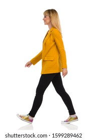Beautiful confident young woman in yellow jacket, black jeans and sneakers is walking, looking away and smiling. Side view. Full length studio shot isolated on white.