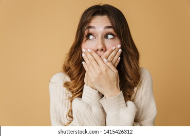 Beautiful confused shocked young woman wearing sweater standing isolated over beige background, covering mouth