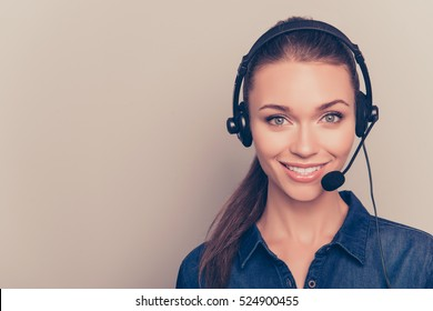 Beautiful consultant of call center in headphones on gray background.