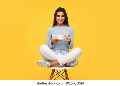 Beautiful content woman sitting on chair in studio holding cup of coffee and smiling at camera.