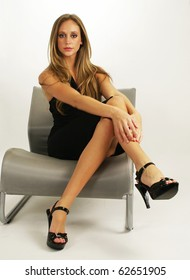 beautiful and content young woman sitting on a chair