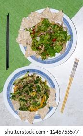 Beautiful cooking design. White tablecloth. Asian food. Salad. Chopsticks.