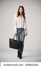 Beautiful cool woman holding black shopping bag and walking on grey background. Fashion girl wearing pink cardigan, jeans and polka dot shirt. Stylish casual woman holding a big bag and looking away.