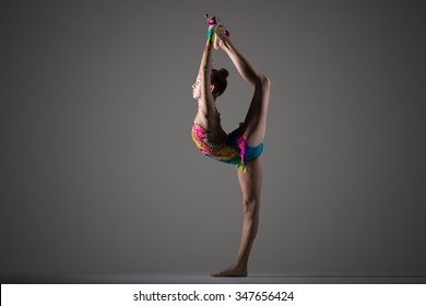 Beautiful cool young fit gymnast woman in colorful sportswear working out, standing on one leg, performing back scale, rhythmic gymnastics backbend element with maces, studio, dark background