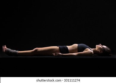Beautiful cool young fit woman in sportswear lying in Shavasana (Savasana, Corpse or Dead Body Posture), resting after practice, meditating, breathing, side view, studio, black background