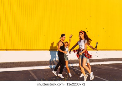 Beautiful cool young jump with confetti on a yellow background, a group of young people celebrating and having fun, summer mood, friends walking in the city in place, party in the Parking lot