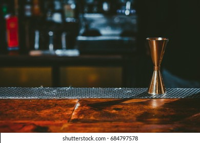 Beautiful copper jigger on wooden bar table