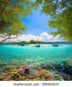 Beautiful coral reef in the background of a tropical desert island Gili Bedis and green mountains. Lombok Island, Indonesia.