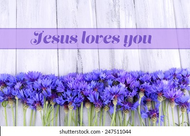 Beautiful cornflowers and text Jesus loves you on wooden background