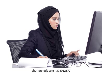 beautiful corporate muslimah woman with office attire showing tired expression while working on desktop computer