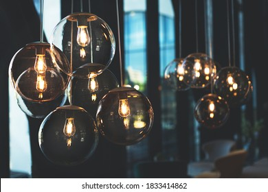 Beautiful and cosy luxury light lamp. Cosy cafe, coffee shop or lounge interior. Vintage and minimal decor. Retro vibes. Many different vintage light bulbs hanging from ceiling. Soft focus.