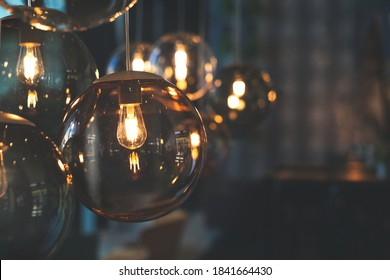 Beautiful and cosy luxury light lamp. Soft focus. Cosy cafe, coffee shop or lounge interior. Vintage and minimal decor. Retro vibes. Dark and moody toning.