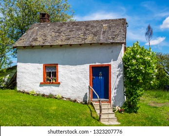 Beautiful cottage in Herresbach, Germany on a sunny summer day, a maypole or Maibaum in the distance