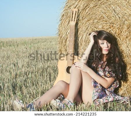 Beautiful country girl in short dress on a summer day basking in the field  on a background of haystacks d14855b71b3