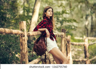 Beautiful country girl travelling and waiting near wooden fence wearing red checkered t-shirt, shorts and leather brown backpack