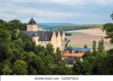 A beautiful country landscape from Franconia, Bavaria. An old castle on a hill with dense forests, arable fields, green forests and blue sky with clouds in the background.
