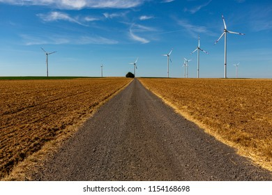 Beautiful country road with white wind turbines with red stripes generating electricity on a bright blue cloudy sky.