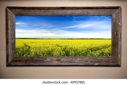 Beautiful countryside image in rustic wooden frame. Mustard field and barn wood create agricultural theme.