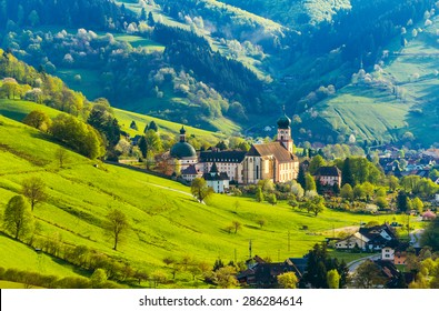 Beautiful countryside mountain landscape with a monastery in village. Germany, Black forest, Muenstertal. Toned