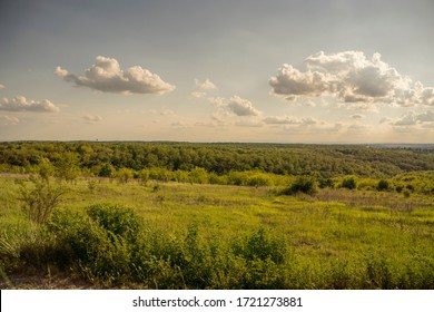 A beautiful countryside scene, with green fields and blue skies featuring a few clouds