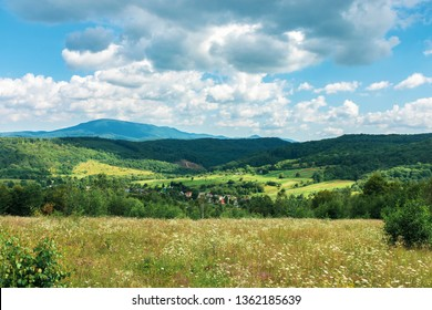 beautiful countryside in summer. wonderful landscape in mountains. rural fields and grassy meadows on hills. village in the distant valley. cloudy weather, dappled light