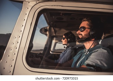 Beautiful couple in aviation headsets is sitting in aircraft ready to fly