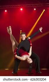 Beautiful couple ballroom dancing on illumination background