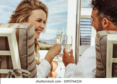 Beautiful couple in bathrobes smiling at each other and toasting wine glasses. Smiling man and woman in bathrobes sitting on deck chairs outdoors and clinking wine glasses.