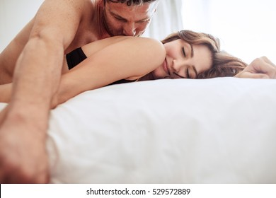 Beautiful couple being romantic and passionate in bed. Man and woman together in bed. He is kissing her.