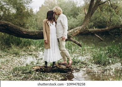 A beautiful couple in the boo style embraces sitting on a branch over the lake