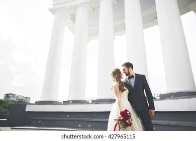 Beautiful couple, bride and groom posing near big white column