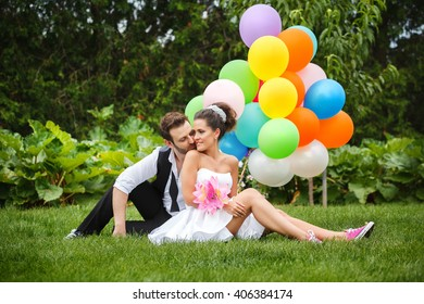 beautiful couple bride and groom sitting on the grass with colored balloons and laughing