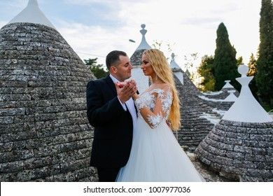 beautiful couple bride and groom in a summer sunny day at roof in Alberobello, Italy
