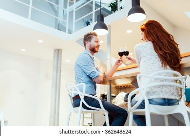 Beautiful couple celebrating moving in to new apartment by toasting wine