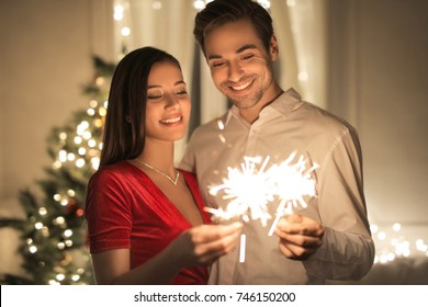 Beautiful couple celebrating New Year's Eve with spark and shiny fireworks