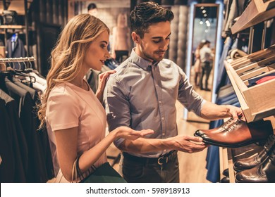 Beautiful couple is choosing classic shoes and smiling while doing shopping in the male store
